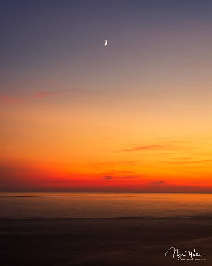 sunset over the Irish sea with the setting moon low in the sky