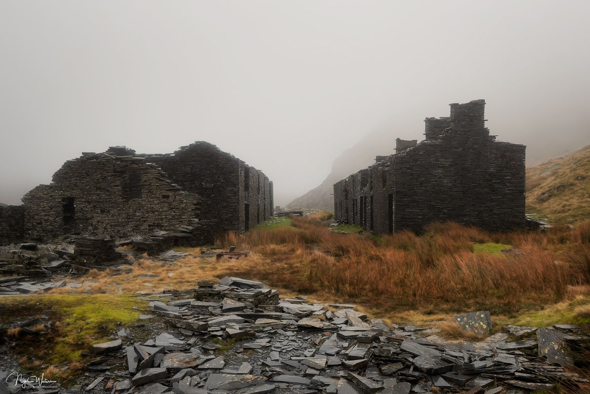 Quarry slate in the foreground with Rhosydd Barracks just beginning to get covered by mist as it rolls in through the valley.
